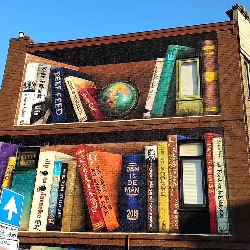 giant 3d bookshelf street art by jan is de man and deef feed 7 Dutch Artists Paint Giant 3D Bookshelf of Neighborhoods Favorite Books