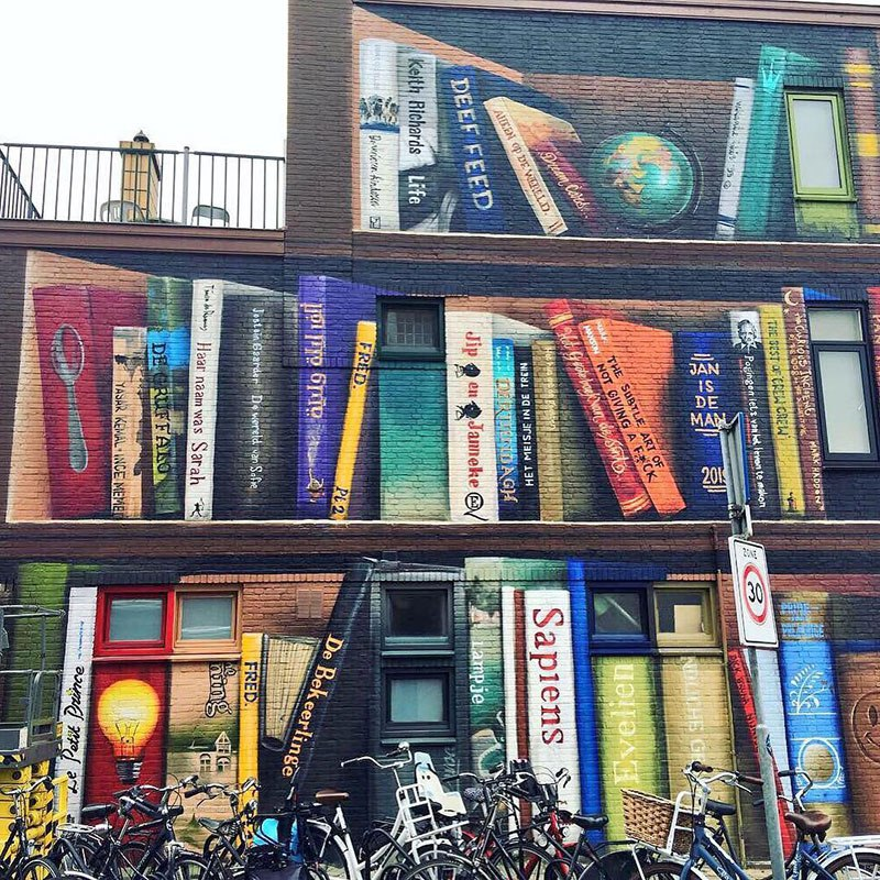 giant 3d bookshelf street art by jan is de man and deef feed 8 Dutch Artists Paint Giant 3D Bookshelf of Neighborhoods Favorite Books